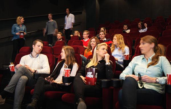 Посетители кинотеатра готовятся к просмотру фильма